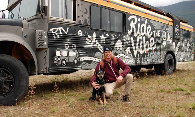 Sam King and his dog, Tiki, in front of a school bus.