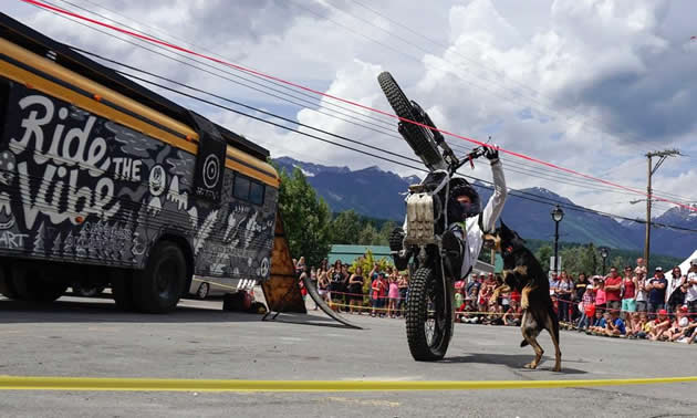 Sam King wheelies with his dog, Tiki, in front of onlookers at a street show.