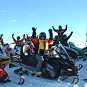 26 women sitting on their parked snowmobiles with their hands in the air