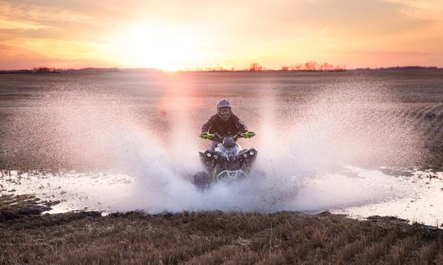 An ATVer splashing through the water on a farm.