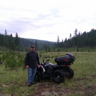 a man standing beside a quad in the backcountry