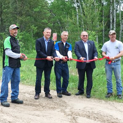 Members of the Eastman ATV Association cutting the ribbon at the grand opening of the Eastman ATV Trail in Sandilands Provincial Forest.
