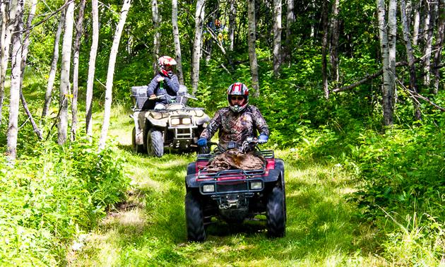 Two ATVer riding down grassy trail in Saskatchewan.