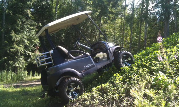 Photo of a tricked-out golf cart climbing a small hill.