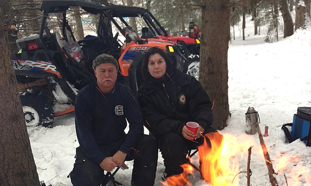 A man and woman kneeling down by a campfire in the wintertime.