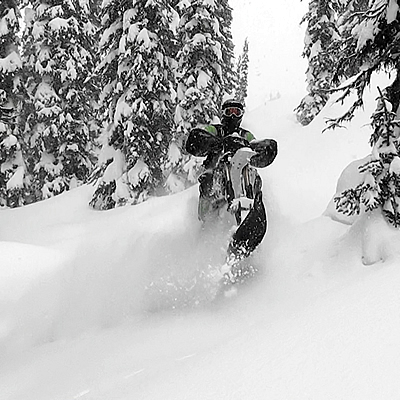 A snow biker plays in the trees.