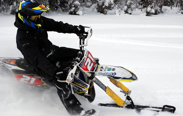 A dirt bike rider carving through the snow on a snow bike.