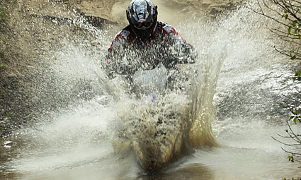 Person riding a dirt bike through water and mud