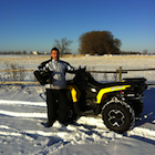 Man standing beside an ATV