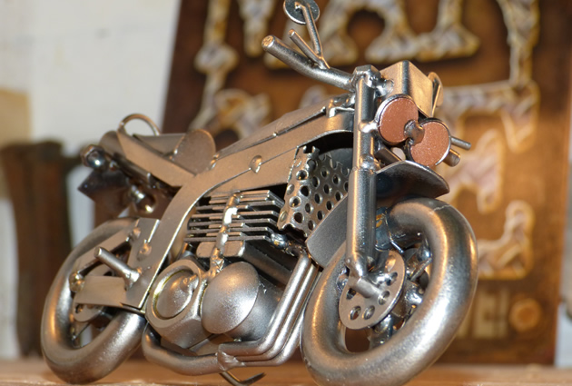 A metal motorcycle figuring with a man cave sign in the back.