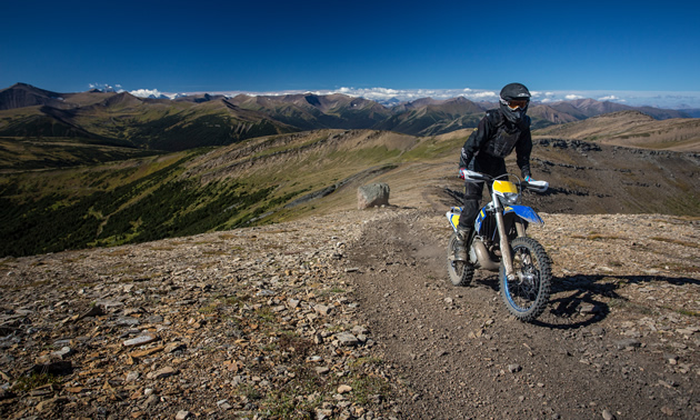 A man on a Husaberg off-road motorcycle riding on a ridge.