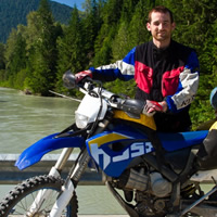A dark haired man standing on a bridge with a dual sport bike.