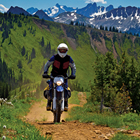 A man riding an off road bike through the mountains.