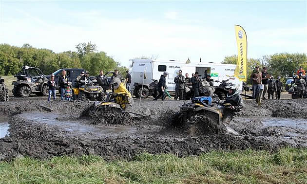 Two ATVers going through a mud bog.