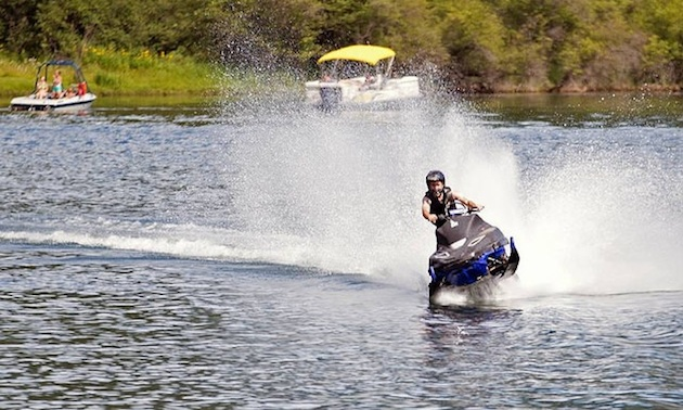 Taylor Fisk riding a snowmobile on water.