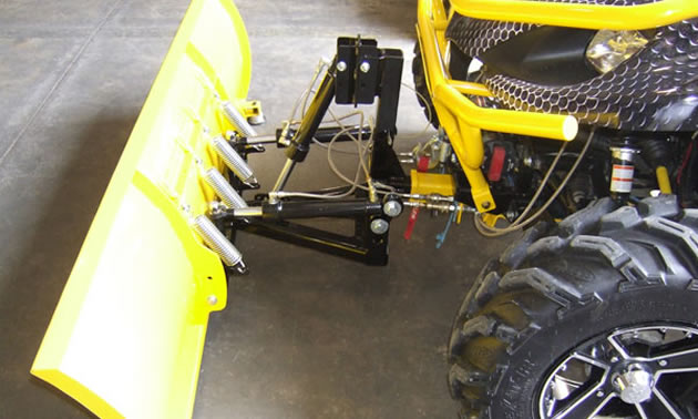 A snow plow on an ATV.