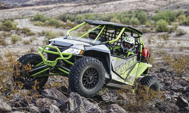 Two men riding in an Arctic Cat Wildcat side by side.