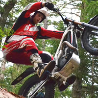 View from the ground up of a man riding a trials bike.