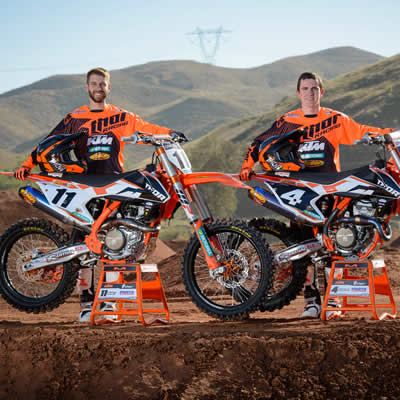 Kaven Benoit and Cole Thompson standing beside their orange KTMs.