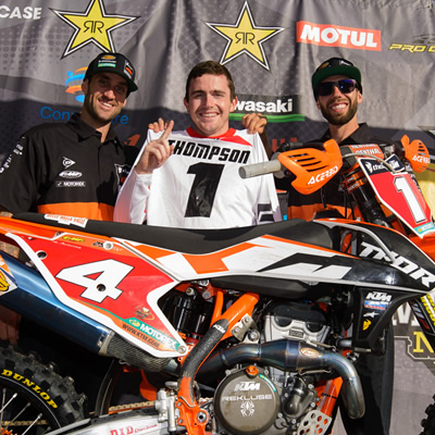 Cole Thompson standing on the podium behind his bike.