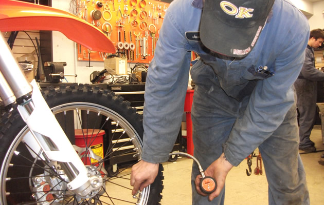 A man in a shop coat checking tire pressure on an orange dirt bike.