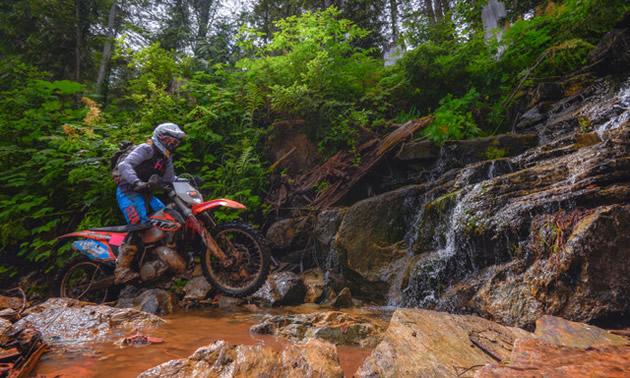 A women on a dirt bike crossing rocks.