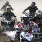 A group of ATVers racing around a corner.