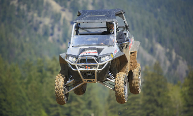 Photo of a guy in a UTV flying through the air.