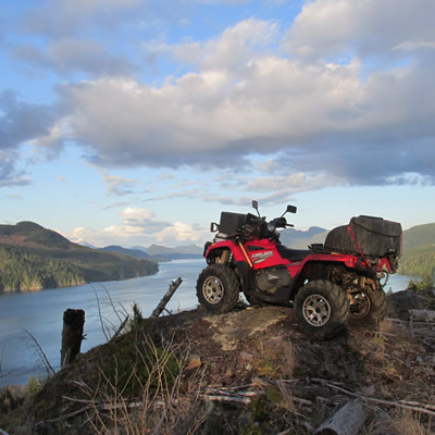 An ATV sitting on top of a mountain overlooking the Johnstone Strait.