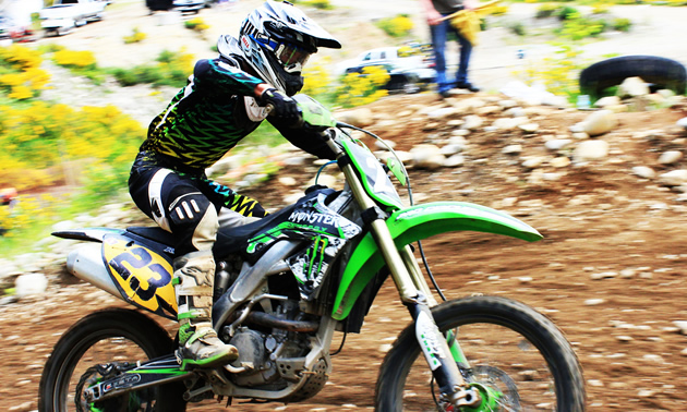 Photo of a guy riding a green dirt bike.