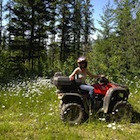 Woman on an ATV in the forest.