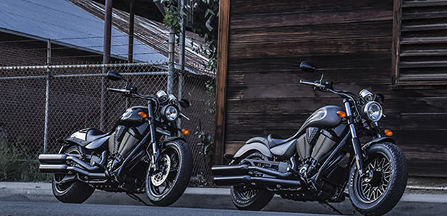 Two black and grey Victory motorcycles.