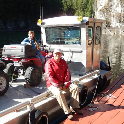 An older couple sitting on a barge with their ATVs on Powell Lake, B.C.