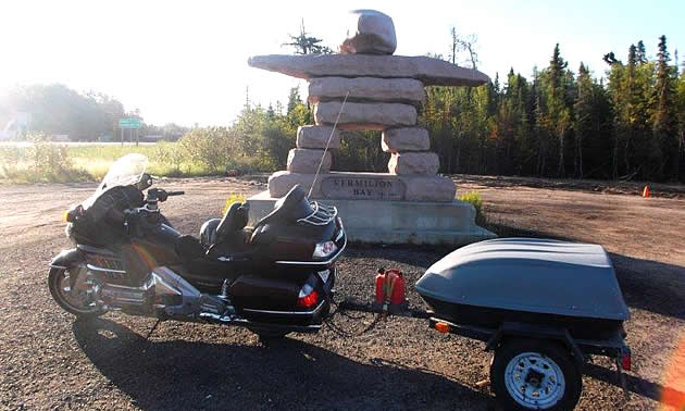A statue of rocks stacked on each other is perched behind a motorcycle with a trailer.