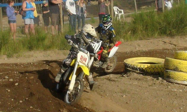Photo of two young kids on dirt bikes coming around a corner.