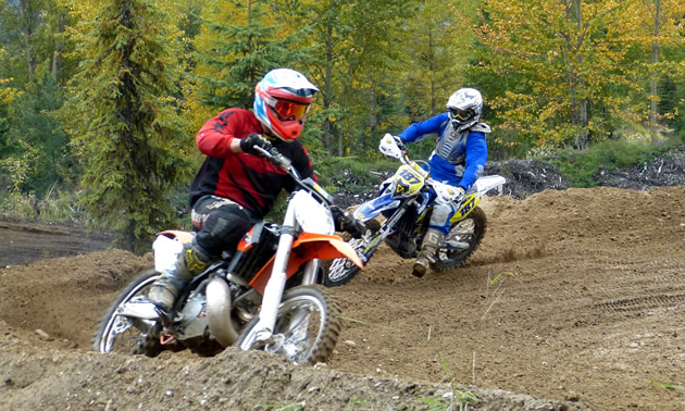 Two motocross racers rounding a corner on the track.