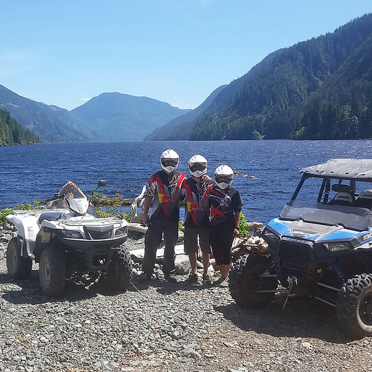 three atv riders standing beside a lake with mountains in the background