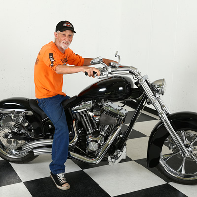 Jerry Wheelz sitting on a black Harley Davidson in the shop.