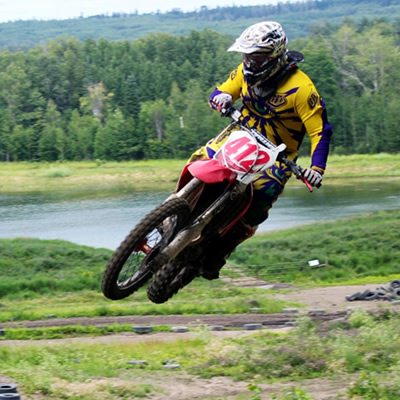 Man on a dirt bike sails over a jump in Whitecourt.