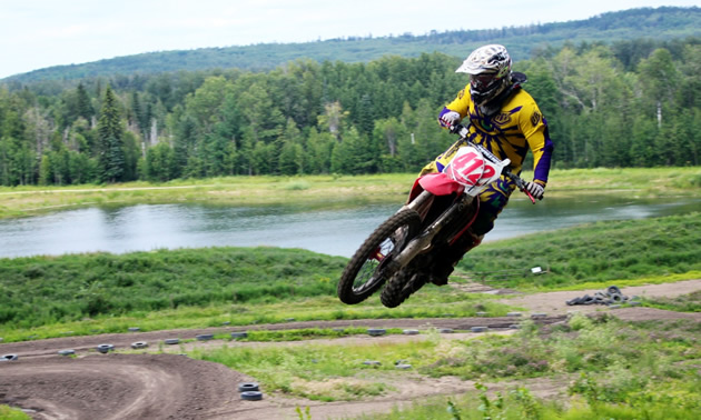 A motorcycle gets massive air in the foreground while a track and swampland is in the background.
