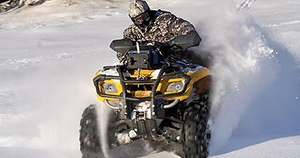Person riding ATV through snow