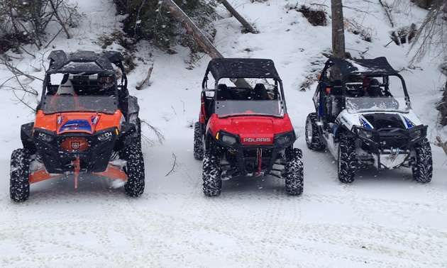 Three sporty looking side by sides lines up in the snow.