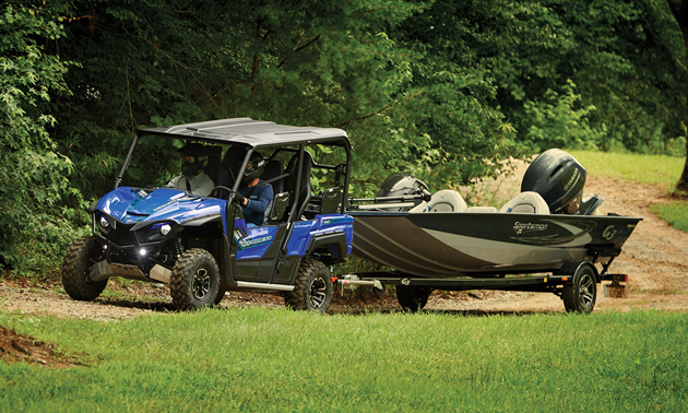Yamaha Wolverine X4 in blue towing a fishing boat.