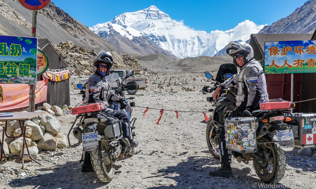Sara and Daniel Pedersen on their motorcycles, looking at Mount Everest.