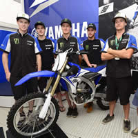 Six young men standing around a new blue dirt bike on the podium.