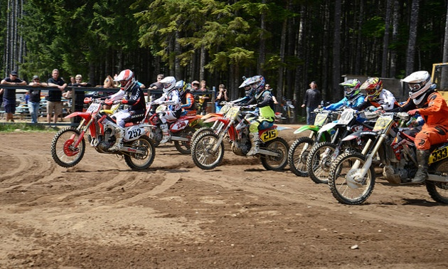 A group of motocrossers coming off the starting line.